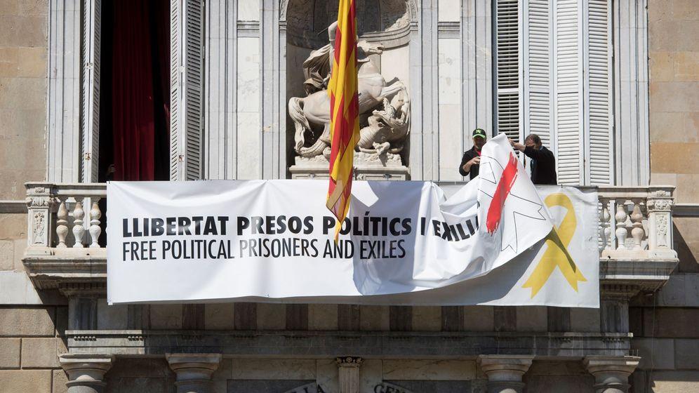Foto: Momento de la retirada de la pancarta del Palau. (EFE)