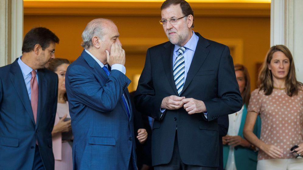 Foto: Fernández Díaz susurrándole a Rajoy. (Reuters)
