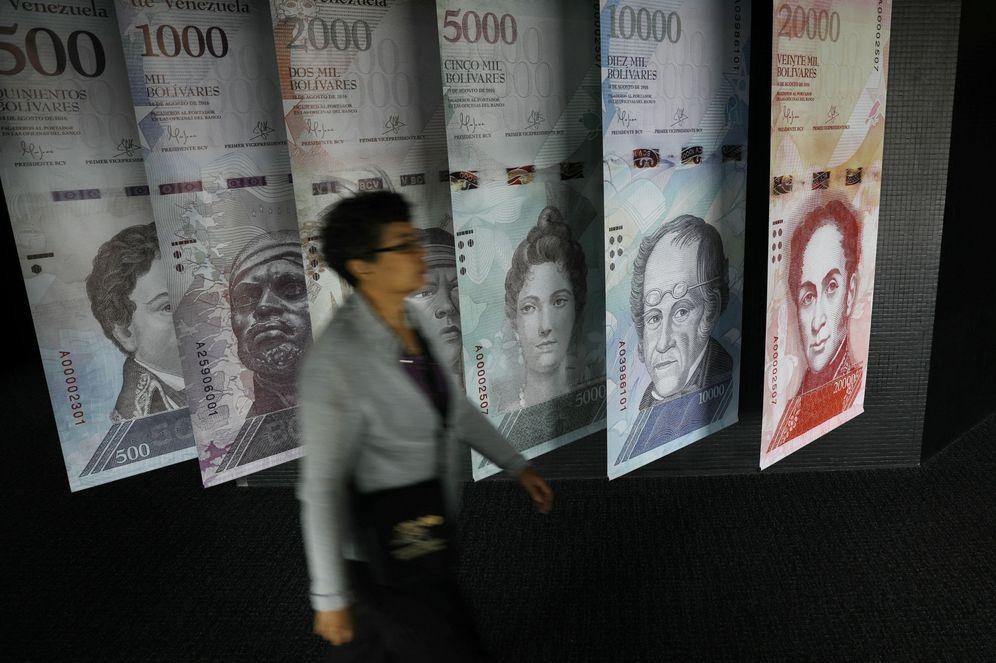 Foto: Una mujer pasa por delante de carteles de billetes de bolívares en el Banco Central de Venezuela, en Caracas, el 23 de mayo de 2017. (Reuters)