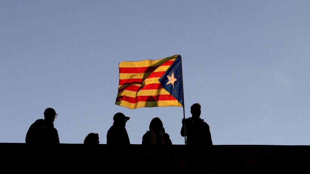 Foto: Varios vecinos ondean una bandera independentista en Barcelona. (EFE)