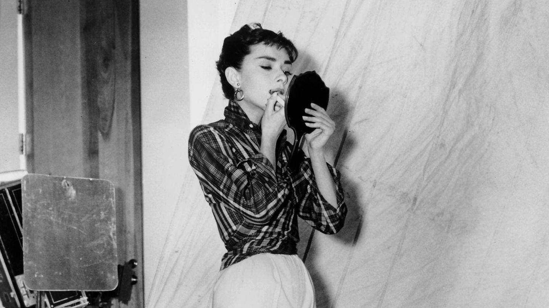 Audrey Hepburn, pintándose los labios en el rodaje de 'Sabrina'. (Cordon Press)