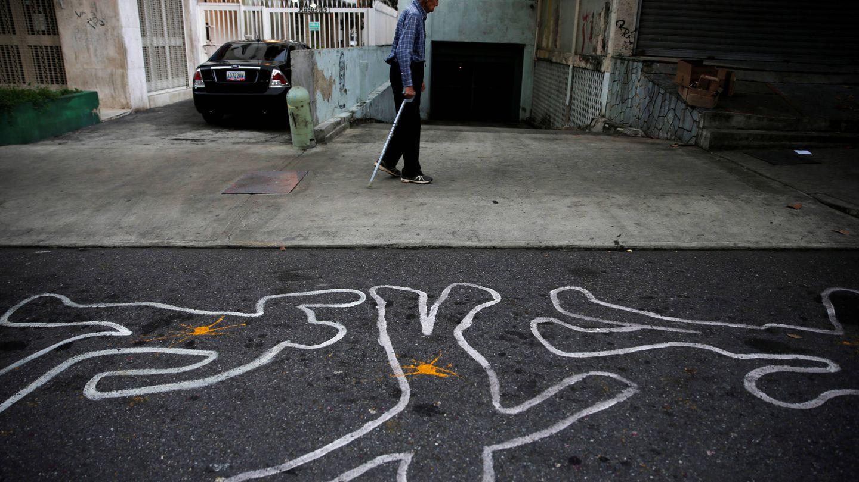 Un hombre camina ante contornos de tiza que representan a víctimas de la violencia, en Caracas. (Reuters)
