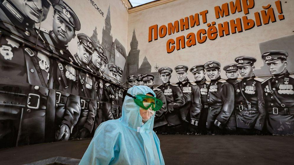 Foto: Una mujer con traje protector, junto a un mural gigante dedicado a la victoria rusa en la Segunda Guerra Mundial. (EFE)