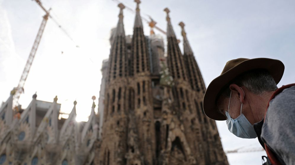 Foto: Una persona con mascarilla pasa ante la Sagrada Familia, en Barcelona. (Reuters)