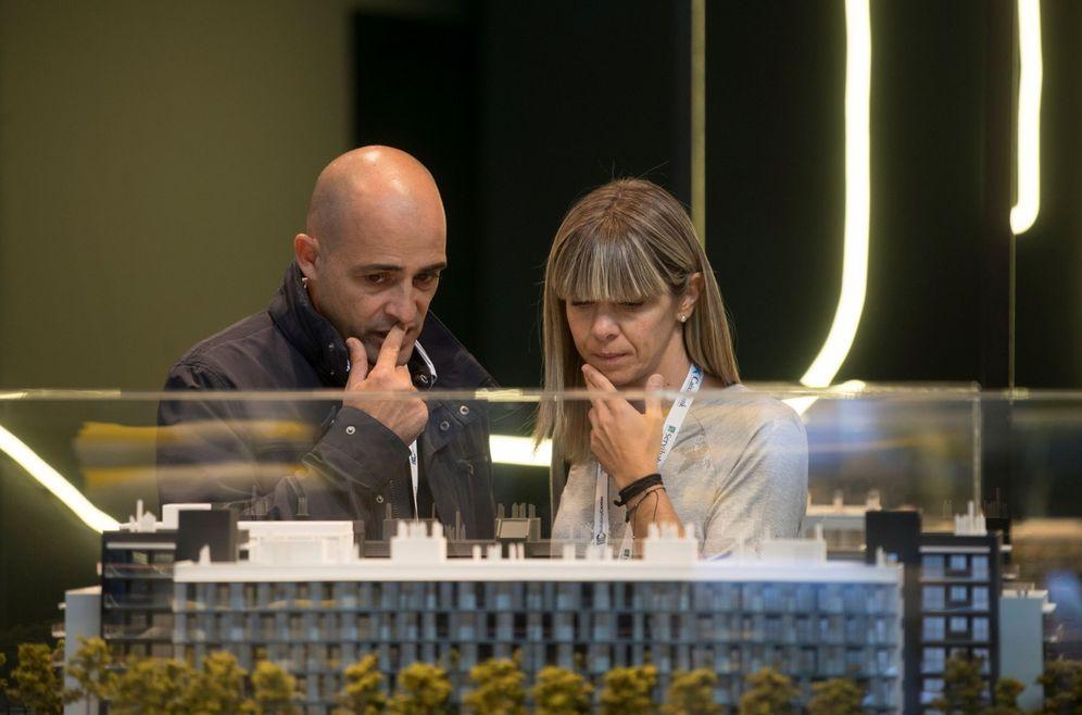 Foto: Visitantes a un salón inmobiliario de vivienda observan la maqueta de un edificio. (EFE)