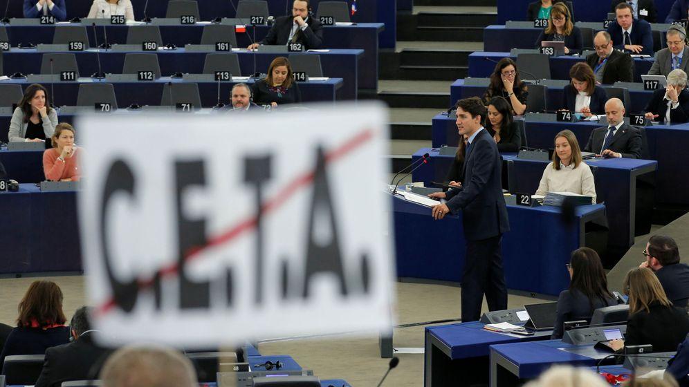 Foto: El primer ministro canadiense Justin Trudeau, visto desde detrás de un poster anti-CETA en el Parlamento Europeo, en febrero de 2017. (Reuters)