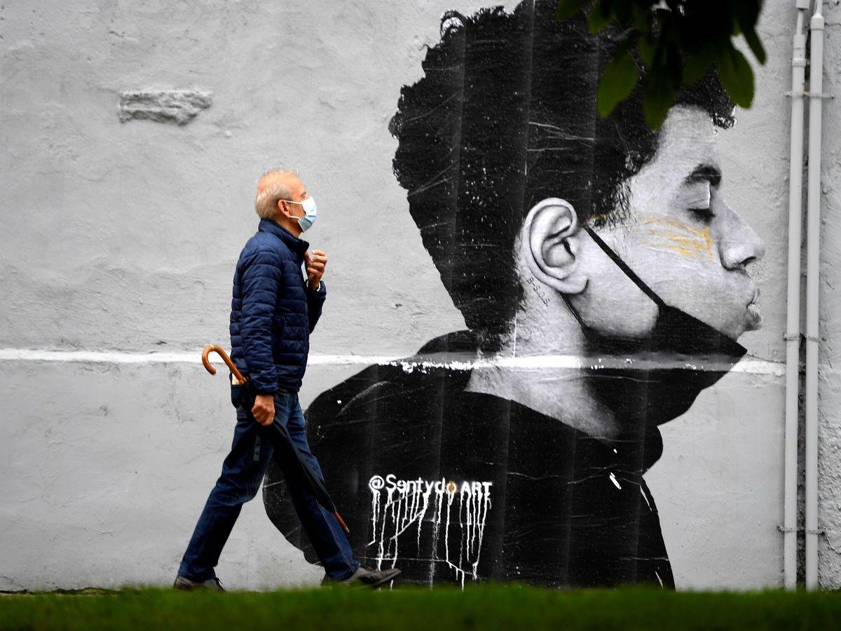 Foto: Un hombre con mascarilla camina por la calle. (EFE)
