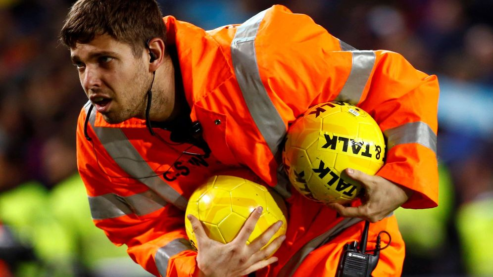 Foto: Un miembro de seguridad recoge dos pelotas lanzadas al césped durante el FC Barcelona-Real Madrid. (EFE)