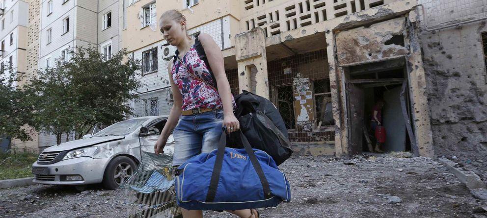 Foto: Una mujer abandona los pisos dañados por los bombardeos en Donétsk. (Reuters)
