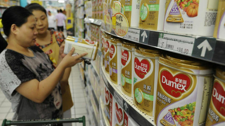 Una trabajadora de un supermercado ayuda a una clienta a comprar leche en polvo Dumex, filial de Danone, en Hefei, en la provincia china de Anhui (Reuters).