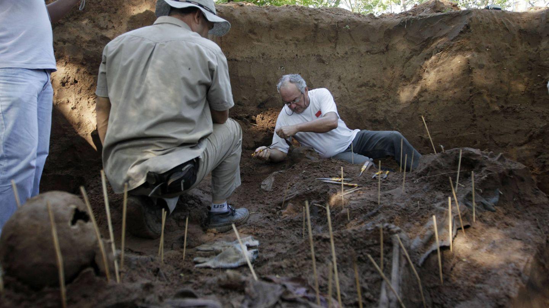 Forenses trabajan con restos humanos descubiertos bajo unas barracas de la policía en Asunción. (Reuters)