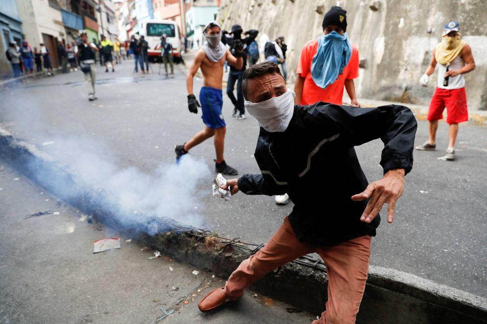 Foto: Un manifestante arroja un bote de gas lacrimógeno durante enfrentamientos con las fuerzas de seguridad en Caracas. (Reuters)