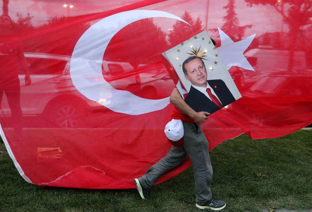 Foto: Un votante de Erdogan sostiene una imagen del presidente ante una bandera turca, en Estambul. (Reuters)