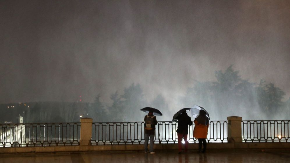 Foto: Varias personas observando las partículas de agua en suspensión debido al fuerte viento en la plaza de Oriente de Madrid la semana pasada. (EFE)