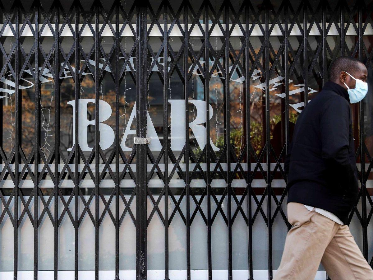 Foto: Una persona pasa por delante de un bar que permanece cerrado en Valencia. (EFE)