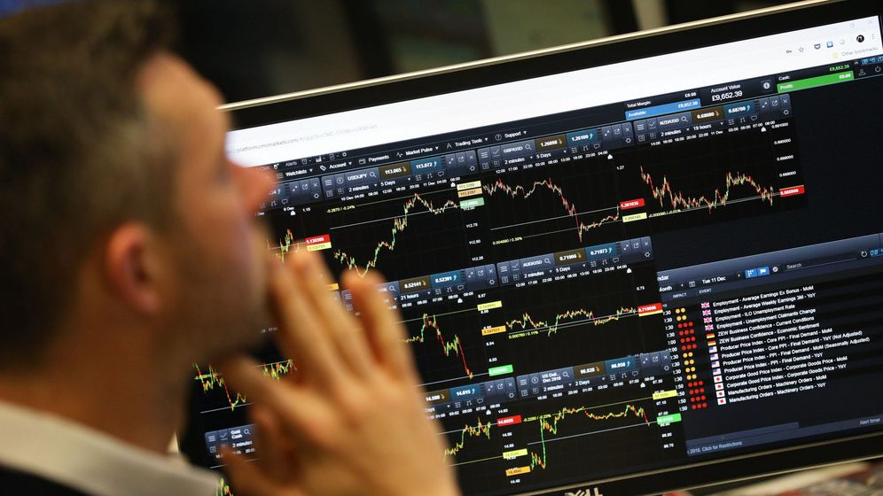 Foto: A trader works as screens show market data at cmc markets in london