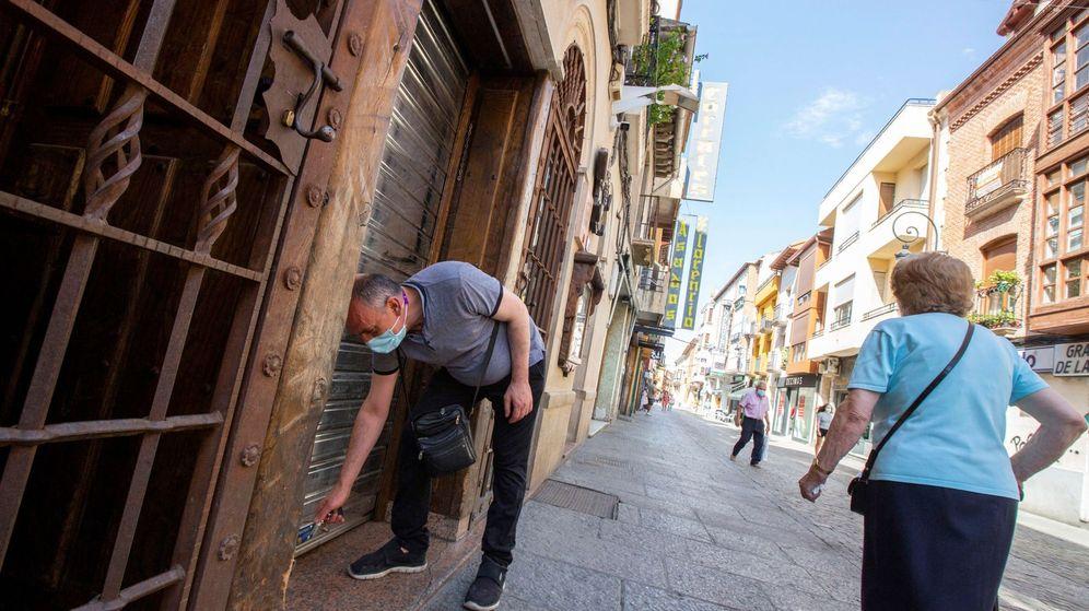 Foto: Un hombre cierra su restaurante en Aranda del Duero donde muchos restaurantes y bares han optado por cerrar. (EFE)