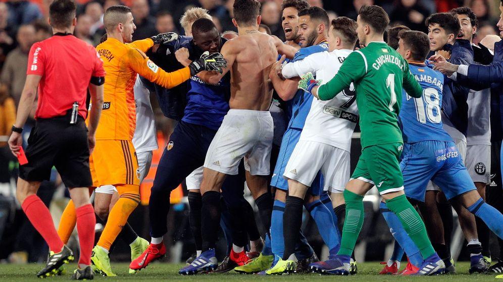 Foto: Los jugadores de ambos equipos, enzarazados a golpes en el medio del campo. (EFE)