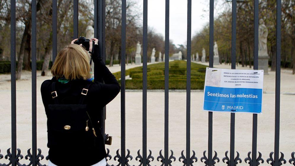 Foto: Una mujer toma una instantánea desde una de las puertas del parque del Retiro, cerrado por el Ayuntamiento de Madrid hasta el próximo viernes. (EFE)