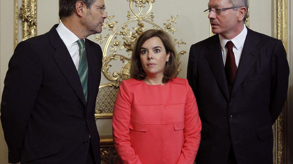 Foto: El ministro de Justicia, Rafael Catalá (i), conversa con su antecesor en el cargo, Alberto Ruiz-Gallardón (d), en presencia de Sáenz de Santamaría. (EFE)