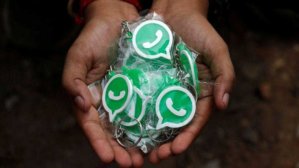 Foto: Una persona sostiene llaveros con el símbolo de WhatsApp. (Reuters)