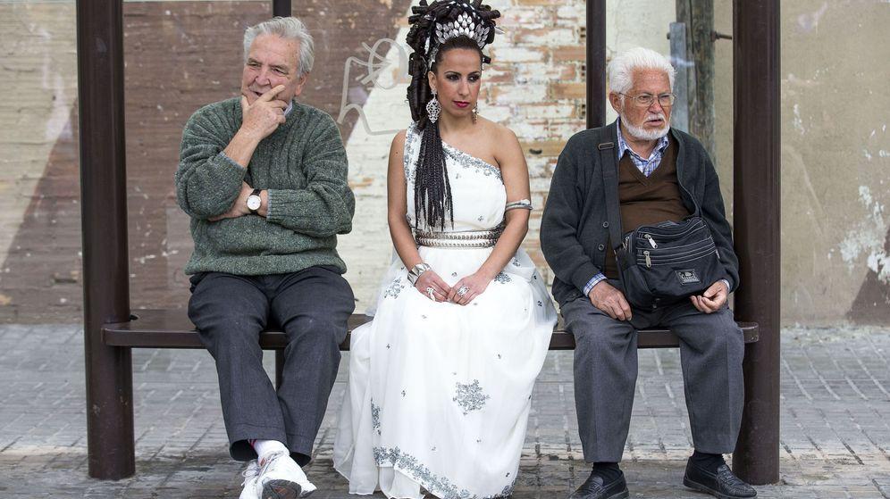 Foto: Tres personas esperan el autobús en el barrio de El Cabanyal, en Valencia. (EFE)