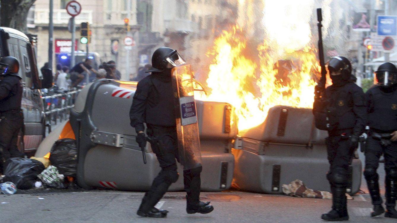 Foto: Varios policías antidisturbios toman posiciones tras unos contenedores en llamas en Barcelona. (EFE)