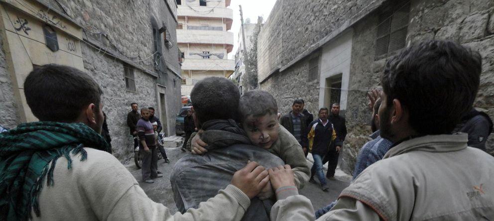 Foto: Un hombre socorre a un niño herido en un bombardeo del régimen este domingo sobre Alepo (Reuters).