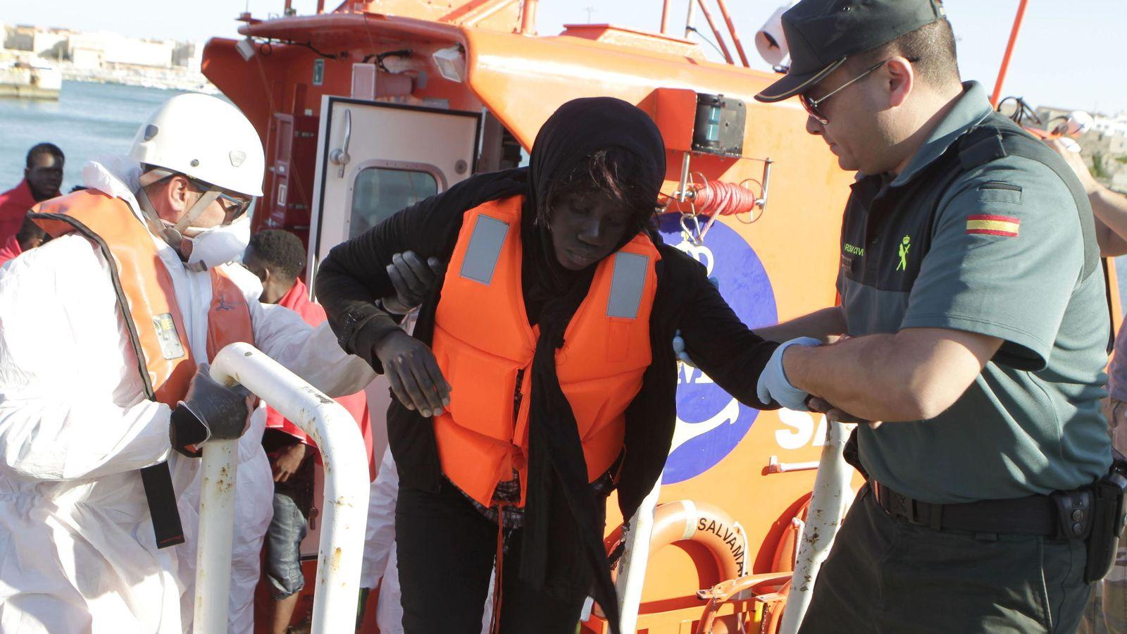 Foto: Un agente de la Guardia Civil y personal de Cruz Roja, ayudan a desembarcar en el puerto de Tarifa (Cádiz) a una mujer de origen subsahariano . (EFE)