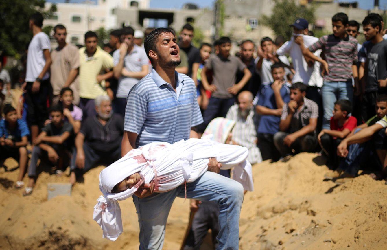 Foto: Un palestino se lamenta mientras carga con el cadáver de una niña de la familia Abu Nejim, muerte durante la ofensiva sobre Gaza (Reuters).