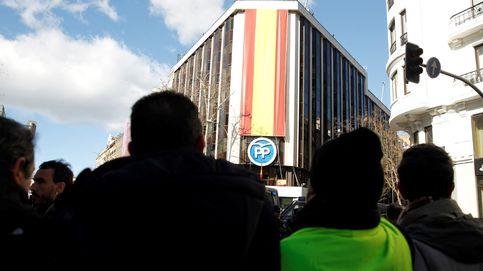 La fachada del PP sufre un desprendimiento al cambiar la bandera por el cartel electoral de Casado