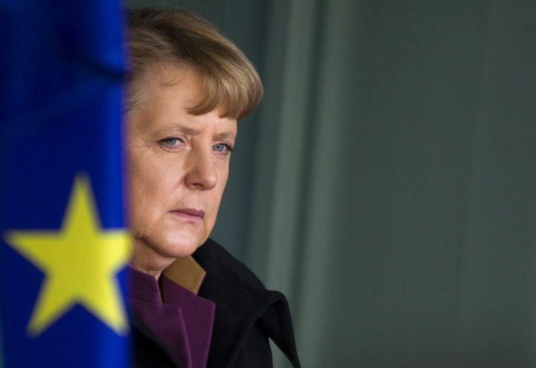 La canciller alemana Angela Merkel junto a una bandera de la Unión Europea en una imagen de archivo (Reuters).