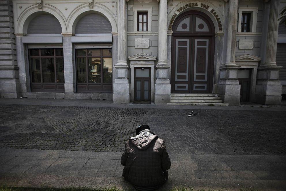 Un hombre se sienta ante una sucursal del Banco Nacional en Atenas (Reuters).