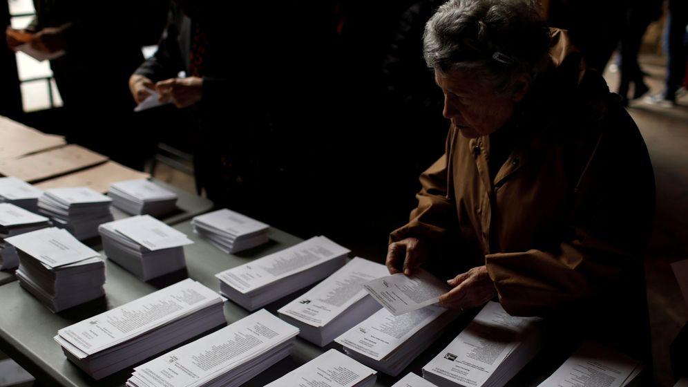 Foto: Una mujer coge una papeleta en las elecciones generales. (Reuters)