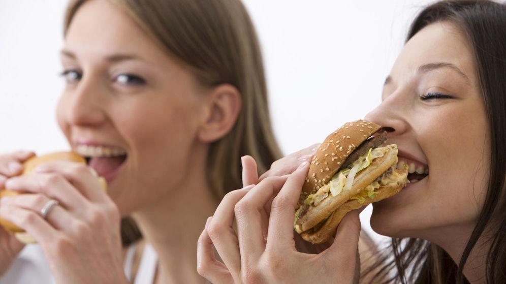 Foto: Dos chicas disfrutan de una hamburguesa. (iStock)