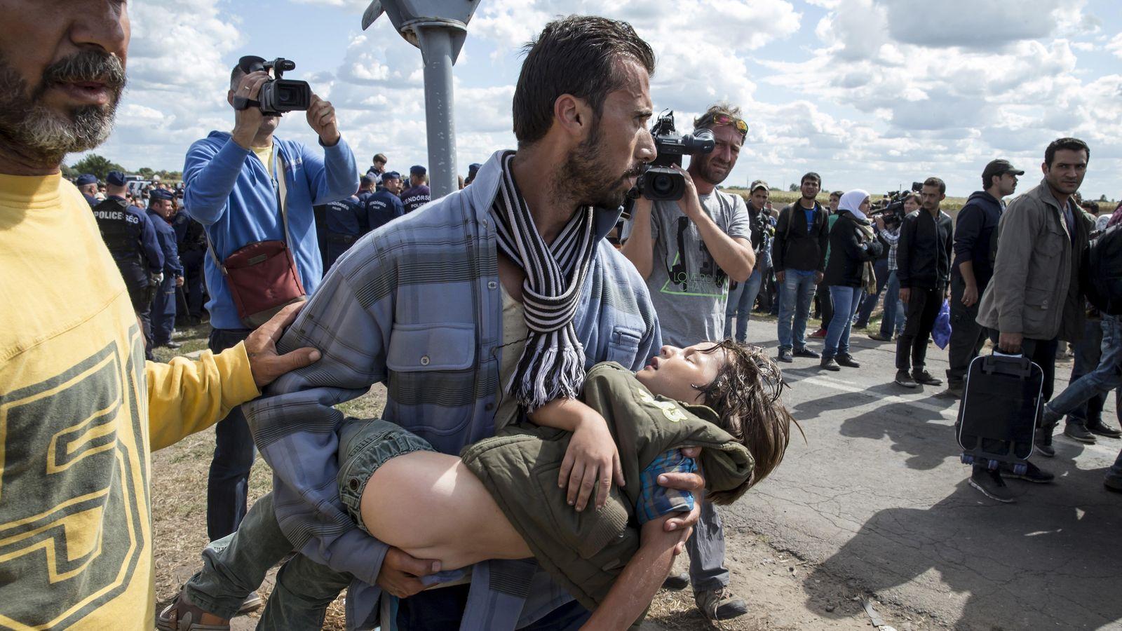 Foto: Un refugiado carga con su hijo enfermo cerca del punto de control en Roszke (Hungría). (Reuters)