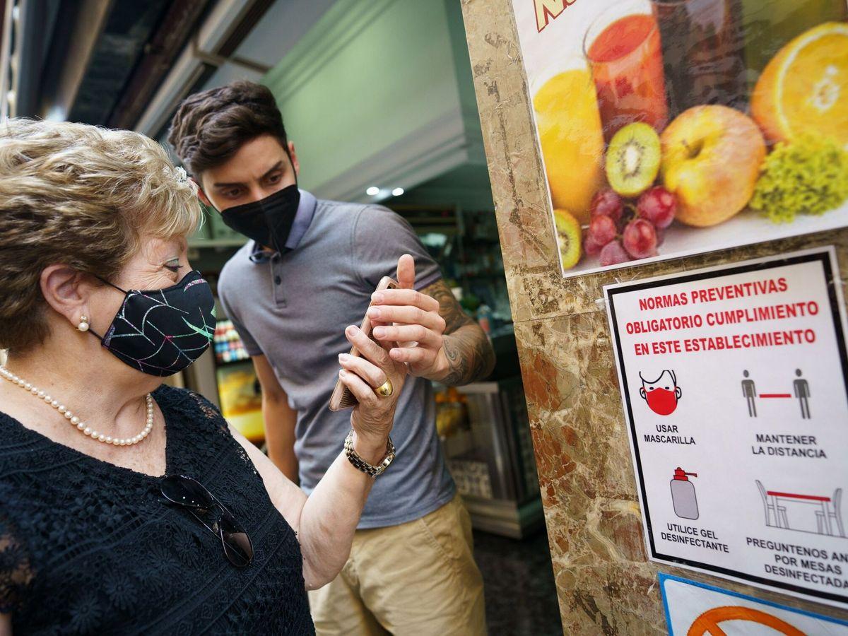 Foto: Un trabajador de una cafetería de Tenerife comprueba un certificado covid. (EFE)