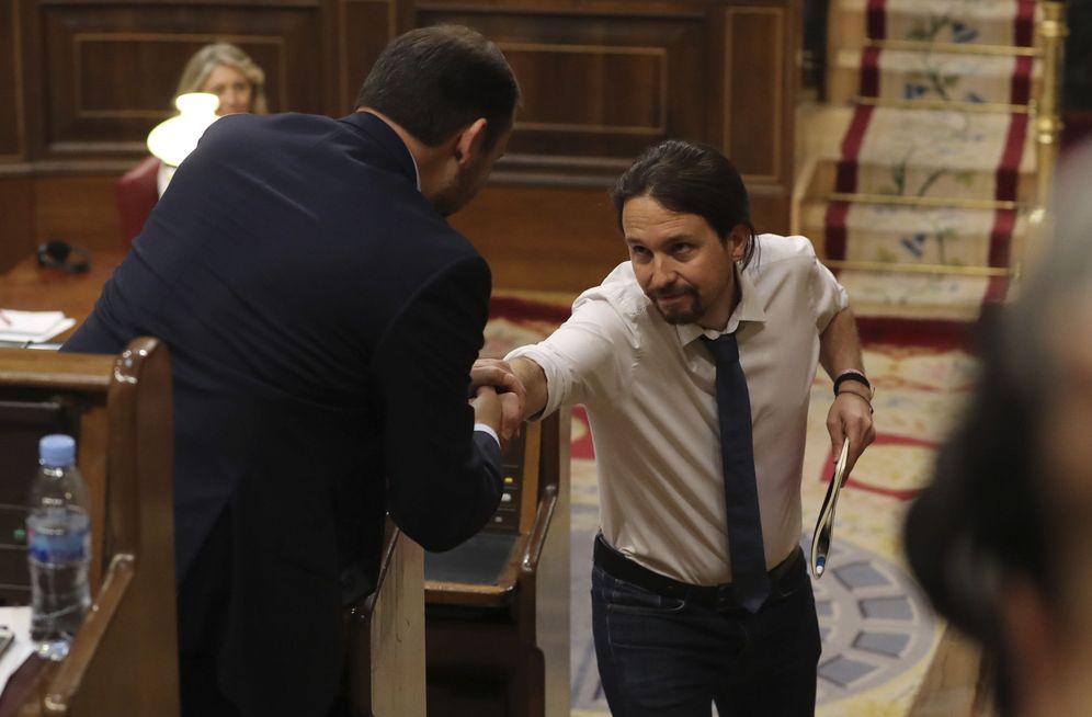Foto: Pablo Iglesias estrecha la mano a José Luis Ábalos durante la segunda jornada de debate de la moción de censura, este 14 de junio. (EFE)