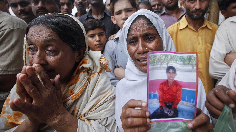 Una mujer sostiene la foto de su hijo mientras los familiares esperan noticias sobre los muertos en el incendio, el 12 de septiembre de 2012. (Reuters)