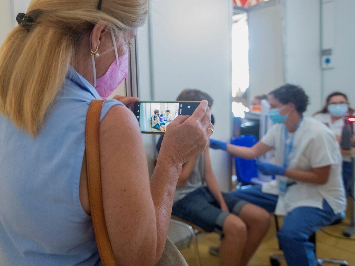 Foto: Una madre fotografía a su hijo mientras se vacuna. (EFE)