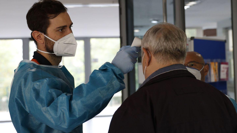 Un sanitario controla la temperatura a un paciente en un centro de salud en Madrid. (EFE)