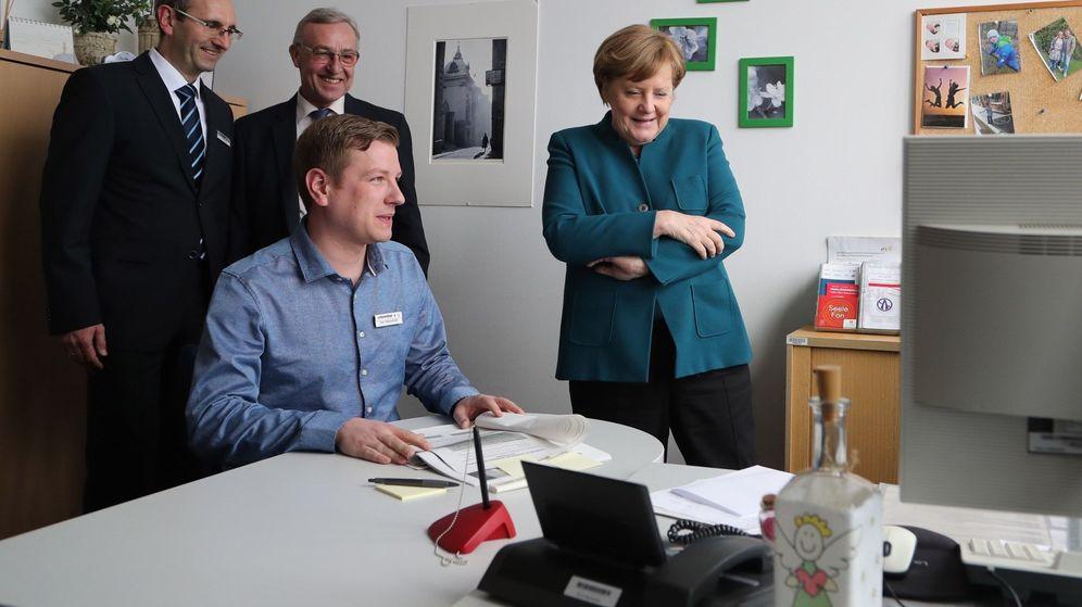 Foto: La canciller alemana, Angela Merkel (d), habla con los trabajadores de una oficina de empleo. (EFE)
