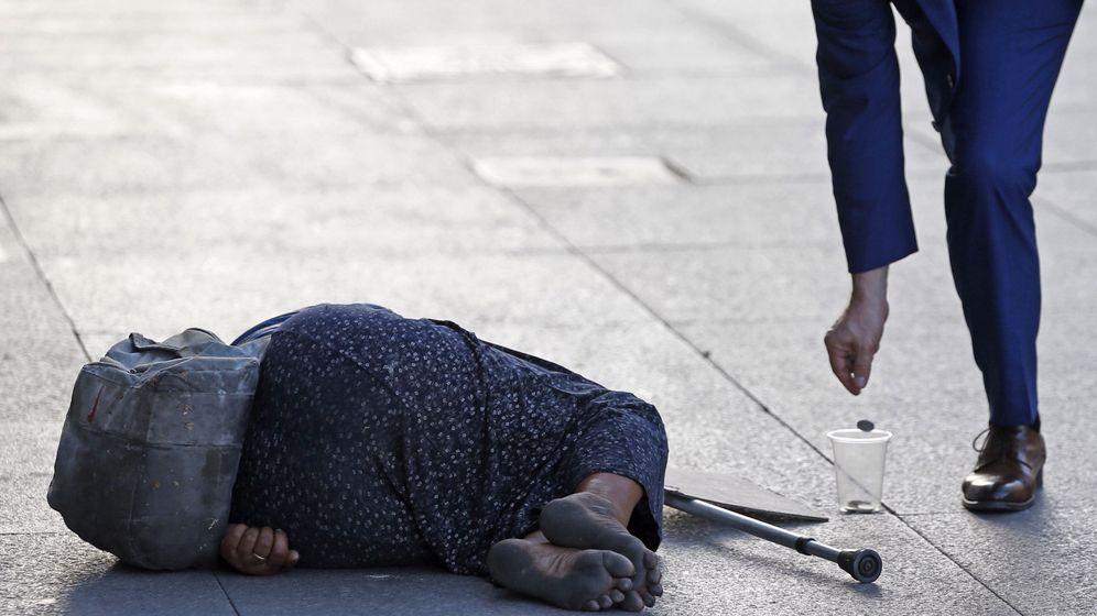 Foto: Un hombre echa una moneda a una mendiga en el centro de Madrid. (EFE)