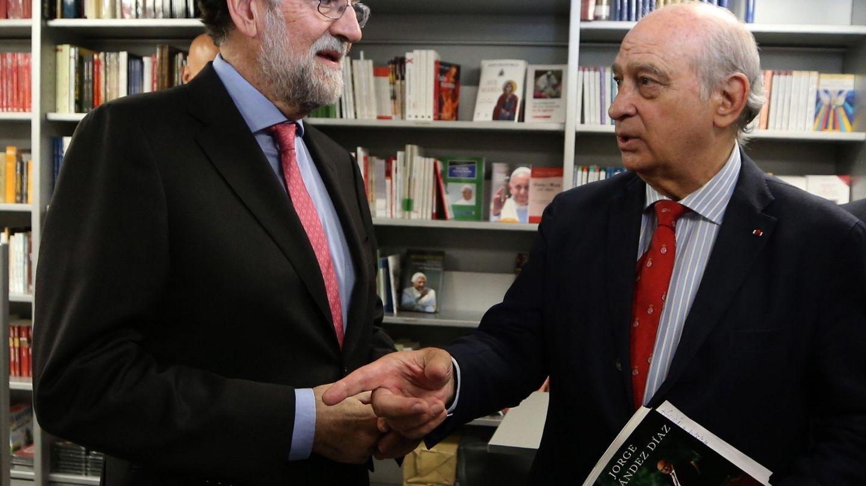 El expresidente Rajoy (i) conversa con el exministro Jorge Fernández Díaz (d) durante la presentación de su libro 'Cada día tiene su afán', en 2019. (EFE)