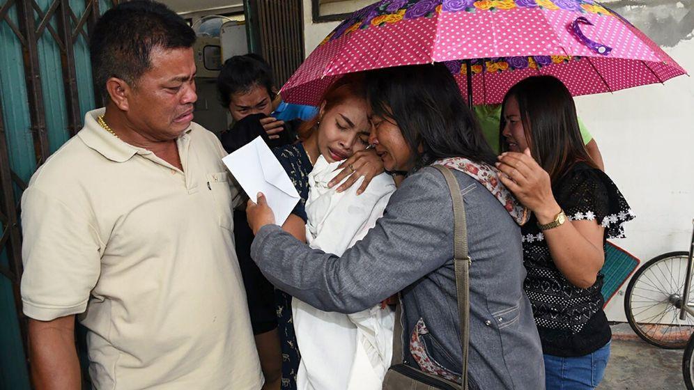Foto: Jiranuch Trirat (2º izq) llora mientras abraza el cadáver de su hija de 11 de meses. (EFE)