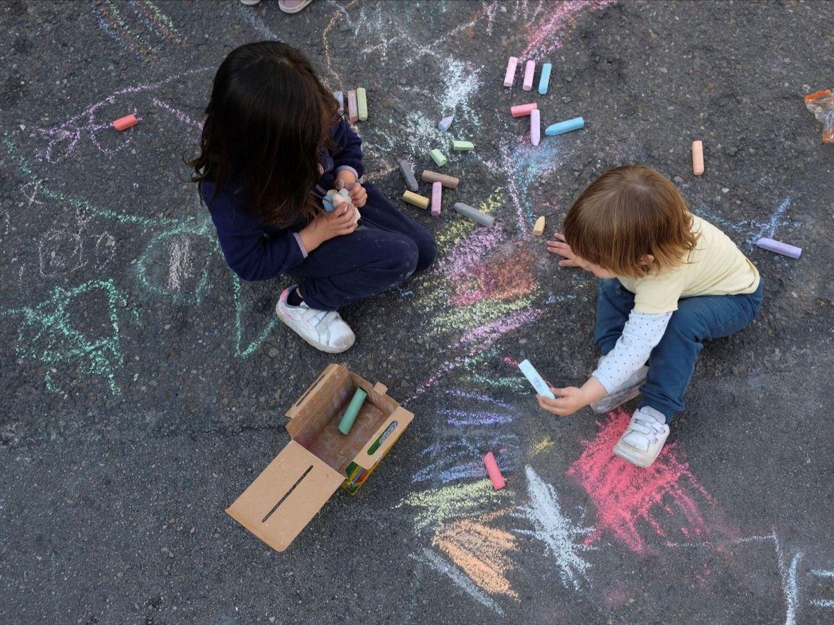 Foto: Dos niños juegan sobre el asfalto de la calle junto al colegio Asunción Rincón, en Madrid. (EFE)