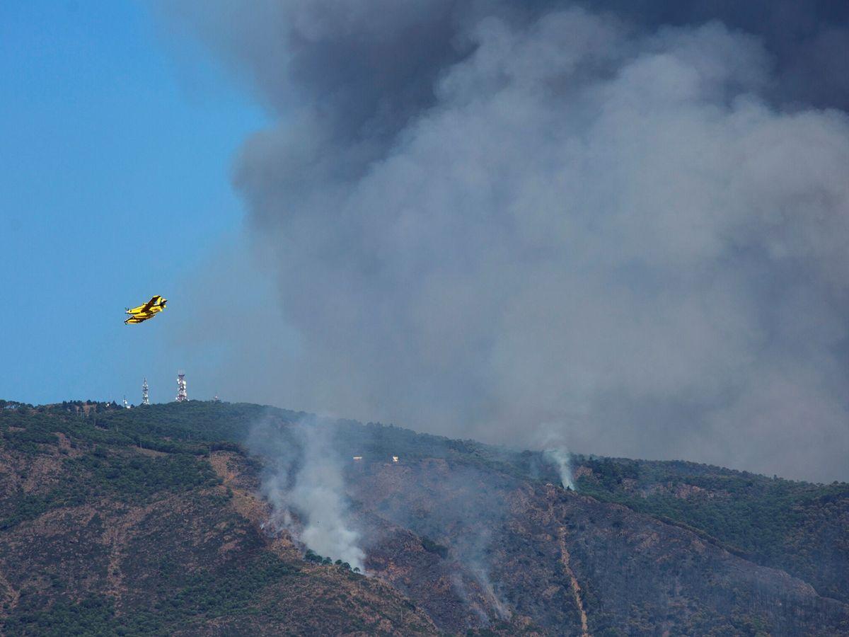 Foto: Un hidroavión sobrevuela la zona quemada por el fuego del incendio de Sierra Bermeja. (EFE)