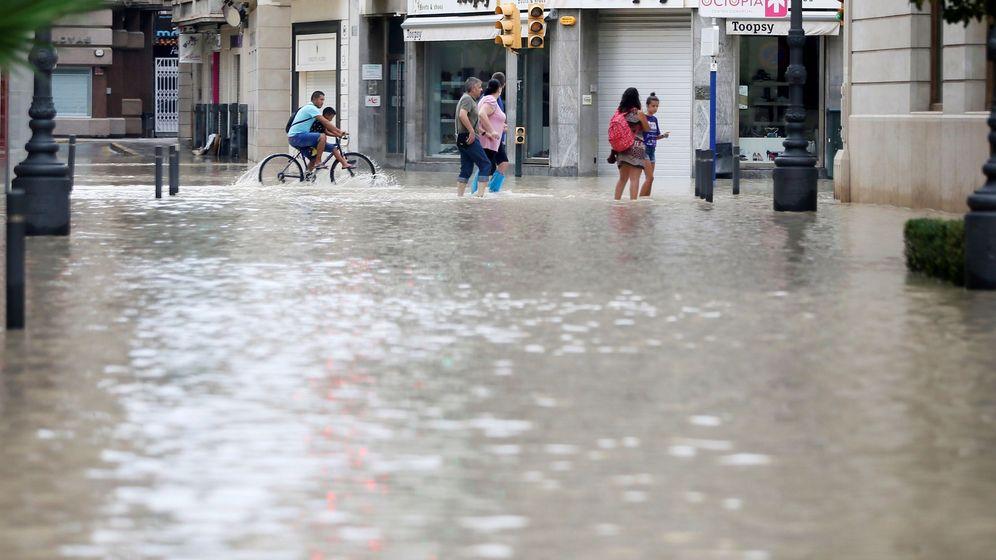 Foto: Varias personas caminan por una calle anegada en Orihuela, una de las poblaciones mas afectadas por el temporal. (EFE)