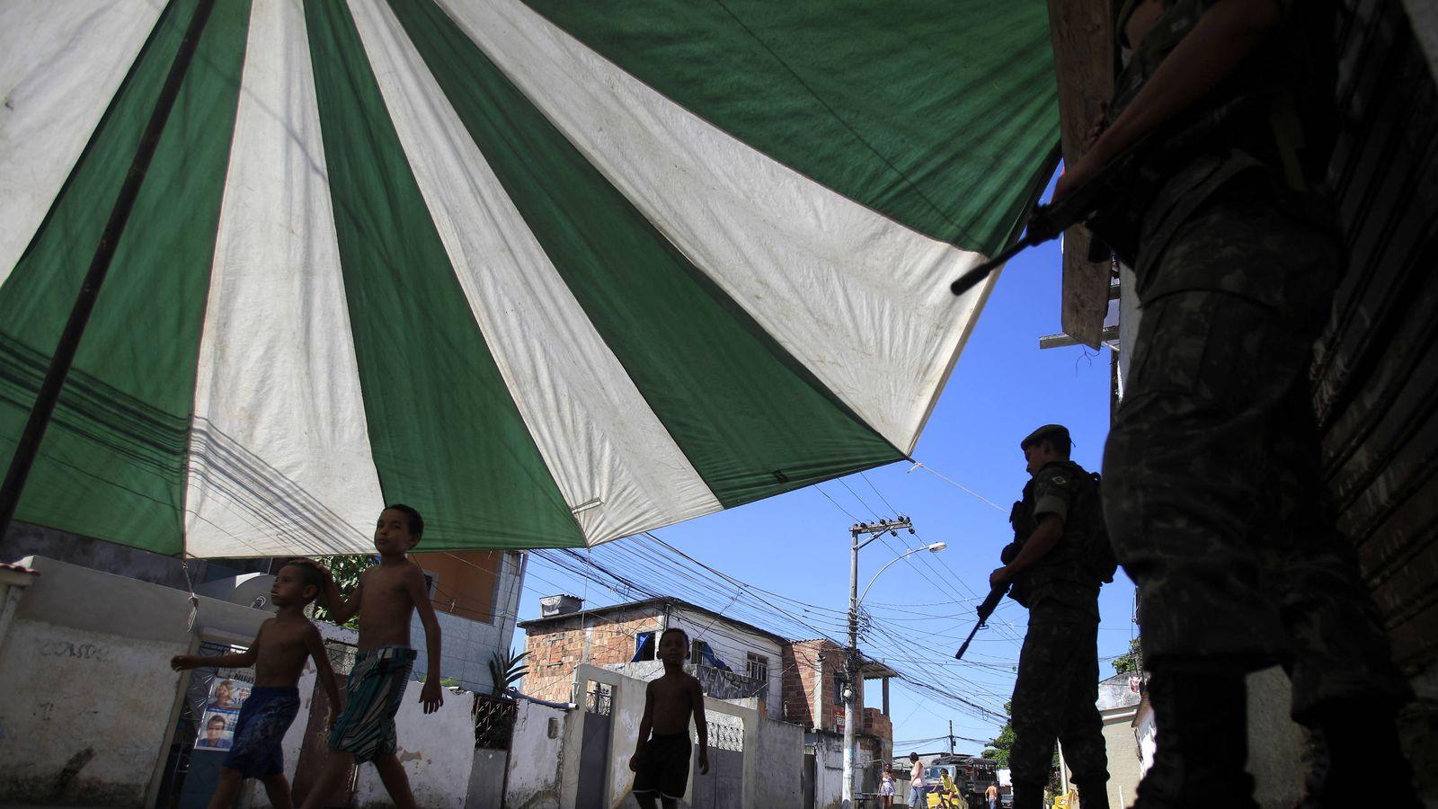 Foto: Unos niños pasan ante soldados brasileños que patrullan por la favela Muquico, en Río de Janeiro. (Reuters)