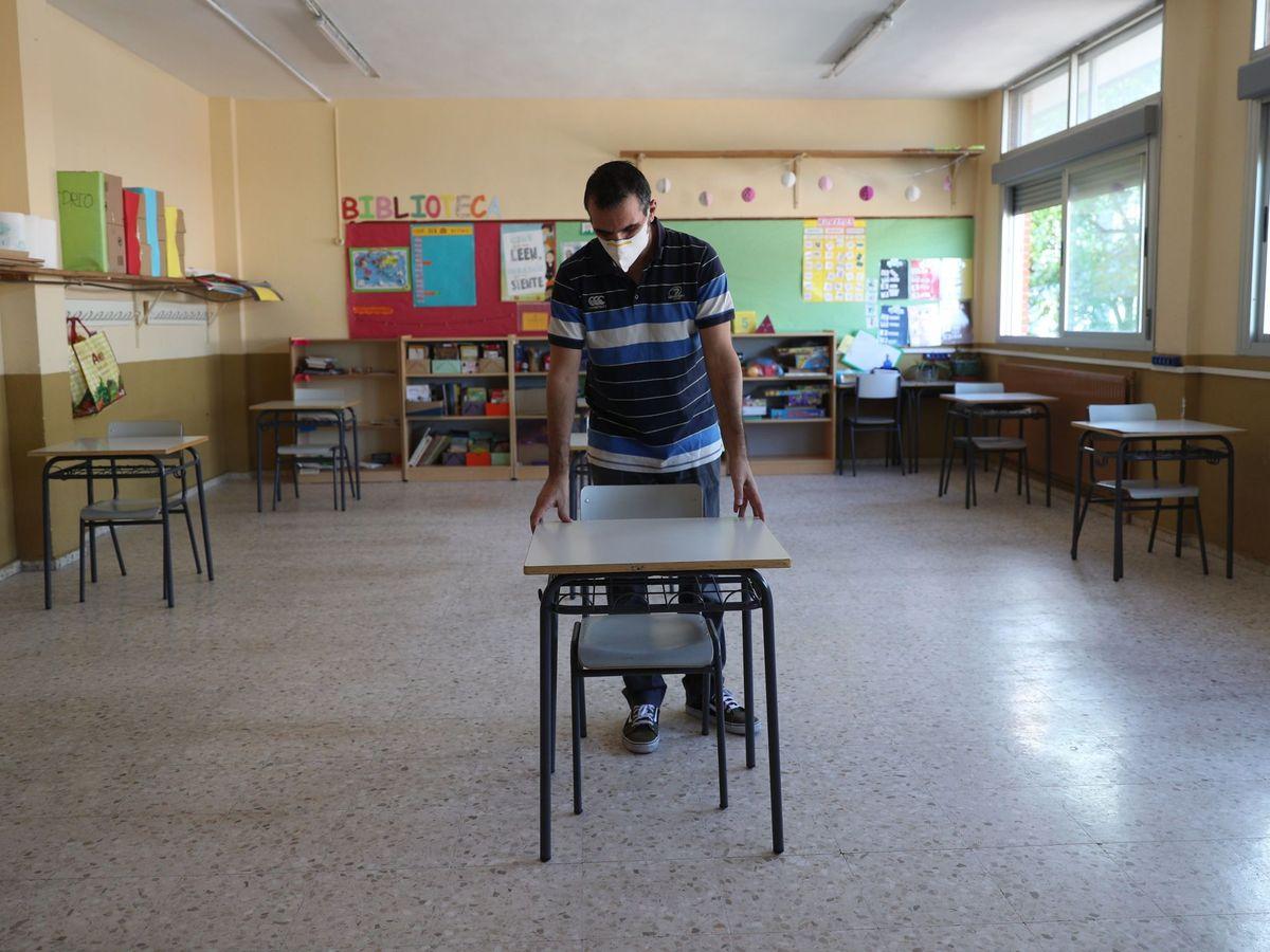 Foto: Un profesor coloca las mesas. (EFE)